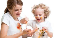 Menina da mãe e da criança que pinta junto foto de stock