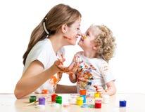 Menina da mãe e da criança que pinta junto fotos de stock