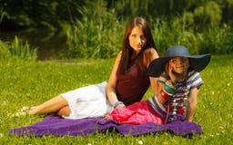Menina da mãe e da filha que tem o piquenique no parque Foto de Stock Royalty Free