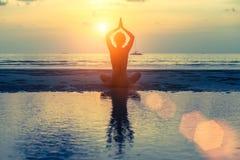 Menina da meditação no mar durante o por do sol Fotografia de Stock Royalty Free