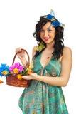 Menina da mola que mostra a cesta com flores Fotografia de Stock Royalty Free