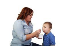 A menina da mulher alimenta o rapaz pequeno Imagem de Stock