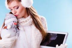 Menina da mulher com tabuleta e o boneco de neve pequeno Inverno imagem de stock
