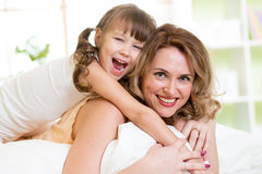 Menina da mulher e da criança na cama que joga e que sorri foto de stock