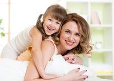 Menina da mulher e da criança na cama que joga e que sorri imagem de stock