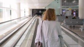 Menina da mulher no aeroporto em correia movente do transporte do cabelo traseiro do gengibre vídeos de arquivo