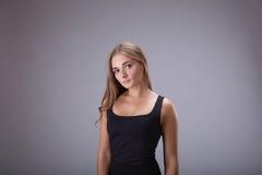 Menina da mulher no retrato preto do estúdio do vestido Fêmea do modelo do cabelo louro no vestido curto preto sobre o fundo cinz imagens de stock