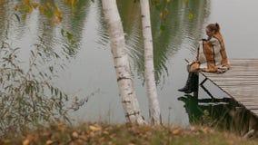 A menina da mulher senta-se no banco de madeira sob o movimento do ramo de árvore do salgueiro no vento perto do lago filme