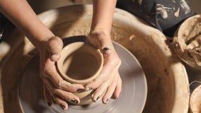 A menina da mulher suas mãos dubla o jarro da parede, esculpe fora da argila no círculo video estoque