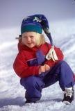 Menina da neve no Snowsuit e no tampão foto de stock