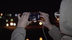 A menina da noite toma na skyline da cidade da noite do telefone na margem Close-up de suas m?os Pressiona seus dedos no t filme