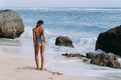 A menina da opinião da parte traseira anda na praia com a garrafa da água fresca em suas mãos imagens de stock