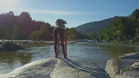 A menina da opinião da parte traseira faz a ioga na pedra contra o rio video estoque