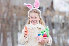A menina da Páscoa com cesta dos ovos e o coelho engraçado enfrentam a expressão na floresta Foto de Stock