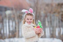 A menina da Páscoa com cesta dos ovos e o coelho engraçado enfrentam a expressão na floresta Imagem de Stock