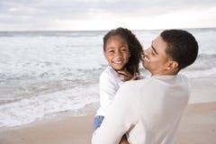 Menina da preensão do paizinho do African-American na praia fotos de stock royalty free