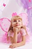 A menina da princesa na coroa e na borboleta cor-de-rosa voa fazendo desejos Foto de Stock