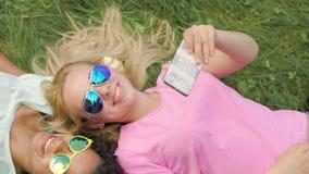 Menina da raça consideravelmente misturada que mostra fotos no smartphone a seu amigo, fim de semana video estoque