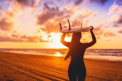 A menina da ressaca com cabelo longo vai a surfar Mulher com prancha em uma praia no por do sol fotografia de stock