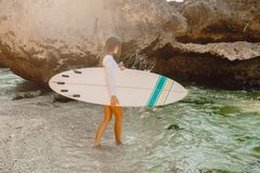 Menina da ressaca com a prancha que vai ao oceano para surfar Menina bonita do surfista fotos de stock royalty free