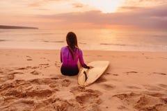 A menina da ressaca com prancha relaxa em uma praia no por do sol ou no nascer do sol Surfar no por do sol imagens de stock royalty free