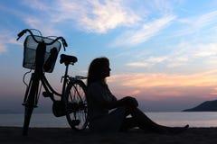 Menina da silhueta com bicicleta Fotos de Stock Royalty Free