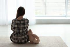 Menina da virada com o brinquedo que senta-se perto da janela dentro fotografia de stock royalty free