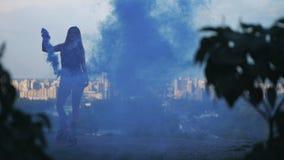 A menina dança em sapatas dos saltos do angoo no fundo da cidade Tem um verificador azul do fumo em suas mãos 4K retardam video estoque