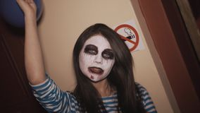 A menina dança, indivíduo com pintura similar da cara e manipula vidros no partido do Dia das Bruxas video estoque