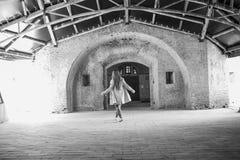 A menina dança movimentos contra a arquitetura velha do fundo imagens de stock