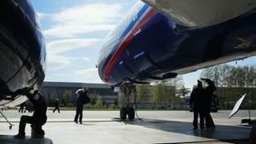 A menina dança no aeródromo perto do trem de aterrissagem do avião de passageiros contra o céu filme