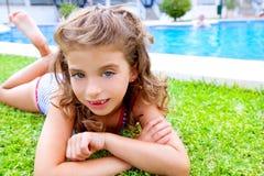 Menina das crianças que encontra-se na grama da associação no verão foto de stock