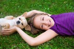 Menina das crianças que joga com o cão da chihuahua que encontra-se no gramado Fotos de Stock Royalty Free