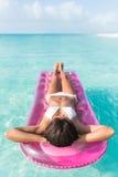 Menina das férias da praia que relaxa na cama do flutuador do oceano fotografia de stock royalty free