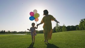Menina das necessidades da mamã e do special que corre com baloons video estoque