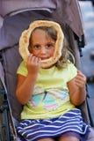 Menina das pessoas de 3-4 anos que come uma filhós grega fotografia de stock
