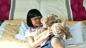 Menina de Ásia que joga o urso de peluche vídeos de arquivo