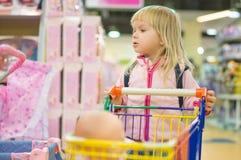 Menina de Adorble com o carro de compra pequeno na alameda dos miúdos Fotos de Stock Royalty Free