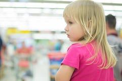 A menina de Adorble senta-se no carro de compra no supermercado Fotografia de Stock