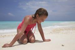 A menina de ajoelhamento que olha um caranguejo minúsculo em uma areia branca encalha Imagens de Stock Royalty Free