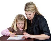 Menina de ajuda da escola da mamã ou do professor com trabalhos de casa Fotografia de Stock