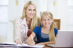 Menina de ajuda da mulher com o portátil que faz trabalhos de casa Imagem de Stock Royalty Free