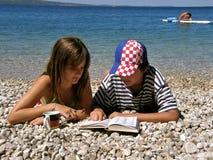 Menina de Alemanha e menino do croata com dicionário Fotografia de Stock Royalty Free
