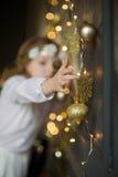 A menina de 8-9 anos na roupa branca com prazer toca em festões do Natal do ouro Fotos de Stock Royalty Free