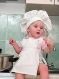 Menina de assento na cozinha fotos de stock royalty free