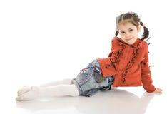 A menina de assento pequena isolada em um branco Fotos de Stock