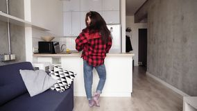 Menina de Attarctive na camisa vermelha da flanela que faz uma dança fora em seu apartamento de estúdio acolhedor do sótão, aprec filme