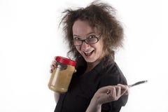 Menina de cabelo crespo que guarda a manteiga e a faca de amendoim Imagem de Stock