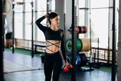Menina de cabelo escuro atlética vestida em suportes pretos do sportswear com água em sua mão perto do equipamento de esporte no  fotografia de stock royalty free