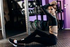 A menina de cabelo escuro atlética vestida na roupa preta dos esportes senta-se no assoalho no gym perto do equipamento de esport imagem de stock royalty free